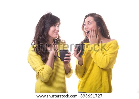 two young women friends in yellow sweater with cups in their hands talking isolated on white background.
