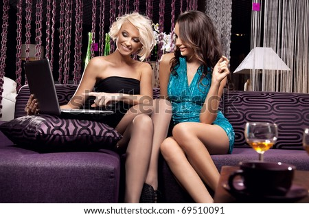 Two young women looking at notebook