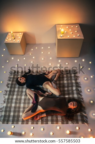 Two young women relax doing yoga asana lotus lying on plaid in cozy room with candles. padmasana variation. Top view