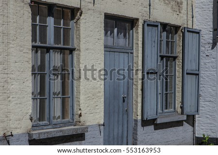 Typical building facade in Bruges, bricks and colorful door and window frames