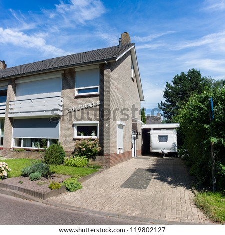 Typical Dutch Semi Detached House situated in a crescent with the blinds down on a sunny day
