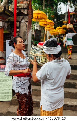 UBUD, INDONESIA - MARCH 2: Child helps his mother during the celebration before Nyepi (Balinese Day of Silence) on March 2, 2016 in Ubud, Indonesia.
