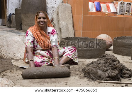 Udaipur (17/02/2016) - Older Indian woman working with clay, making a tandoori oven. She is looking straight into the camera.