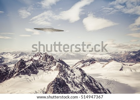 UFO spaceship flying over Alaskan mountain peaks with blue sky and clouds.