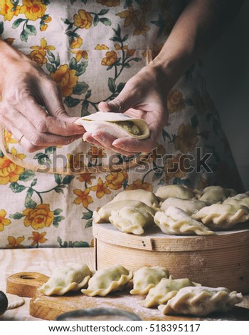 Ukrainian traditional bakery products - Making pierogies by female hands. Rustic style. Retro Photo