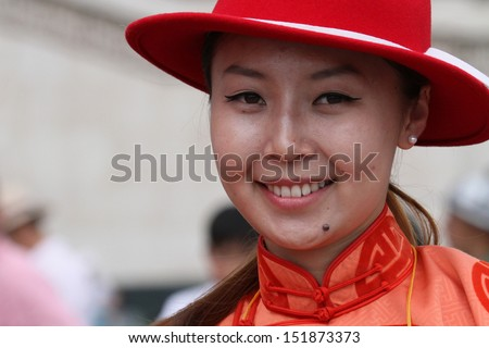 ULAN BATAAR, MONGOLIA, JULY, 20 - Young smiling woman in red clothes during Naadam, on July 20, 2013 in Ulan Bataar, Mongolia. Naadam is inscribed on the List of the Cultural Heritage of Humanity
