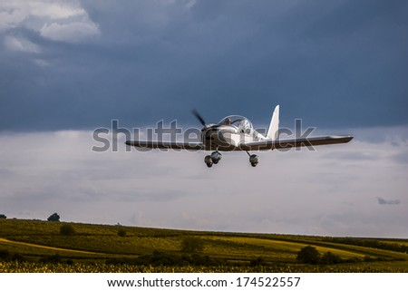 Ultralight airplane during landing at a village small airfield