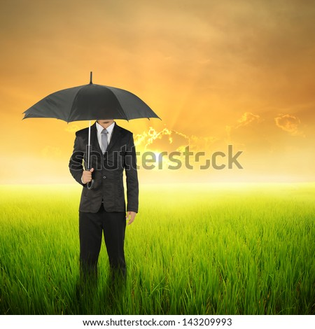 Umbrella woman standing to sunset in grassland with  umbrella