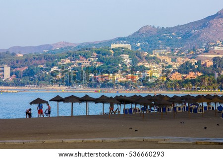 umbrellas at sunset on the beach Malagueta in Malaga Spain