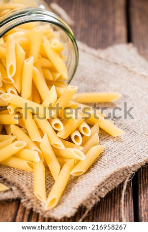 Uncooked Penne (detailed close-up shot) on rustic wooden background