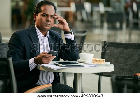 Unhappy businessman drinking coffee and checking smartphone