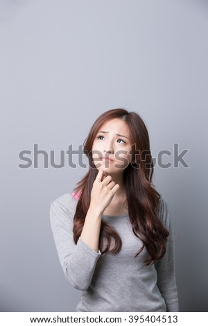 unhappy woman think something isolated on gray background, asian beauty