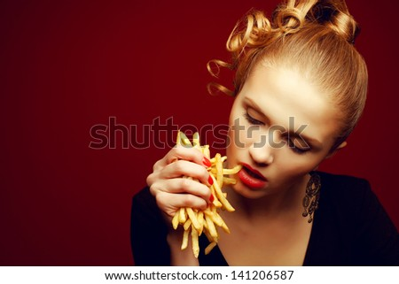 Unhealthy eating. Junk food concept. Portrait of fashionable young woman holding (eating) fried potato (fries, chips), looking down and posing over red background. Close up. Copy-space. Studio shot
