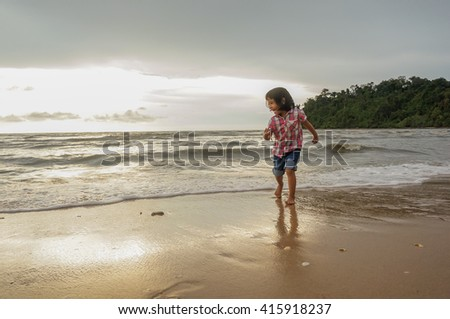 Unidentified young girl playing at the beach on late evening