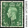 UNITED KINGDOM - CIRCA 1950 to 1952: An English One and a Half Pence Green Used Postage Stamp showing Portrait of King George VI, circa 1950 to 1952 - stock photo
