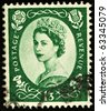 UNITED KINGDOM - CIRCA 1952 to 1965: An English One Shilling and Three Pence Green Used Postage Stamp showing Portrait of Queen Elizabeth 2nd, circa 1952 to 1965 - stock photo