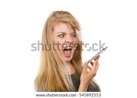 Unpleasant conversation, bad relationships concept. Screaming furiously angry young blonde woman talking on phone. Studio shot isolated