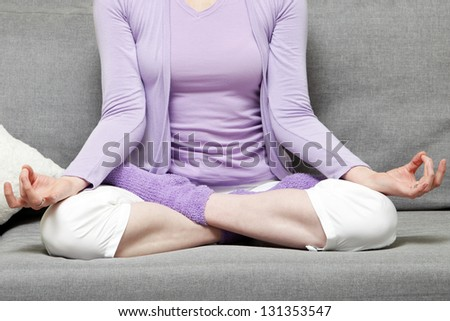 Unrecognizable woman doing yoga pose over the grey background