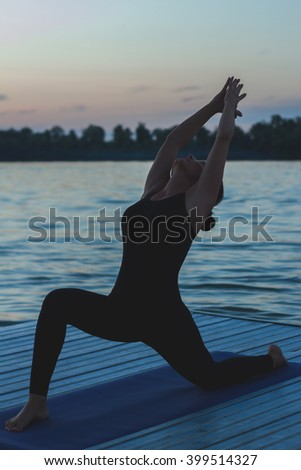 Unrecognizable young woman in low lunge position on pier at twilight
