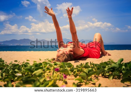upper view blond girl in red frock lies on sand lifts palms up looks upwards near foreground green creepers