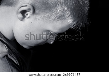 Upset abused frightened little child (boy),  close up horizontal dark portrait with copy space