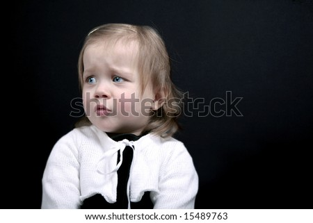 Upset baby girl on black background