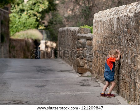 Upset baby girl stand near bricked wall.