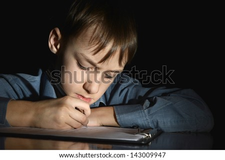upset little boy on a black background