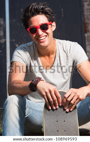 Urban asian man with red sunglasses and skateboard sitting on stairs. Good looking. Cool guy. Wearing grey shirt and jeans.