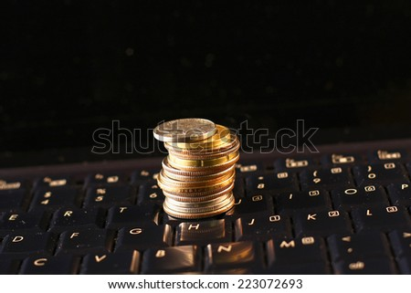 US coins on computer keyboard. Concept of e-commerce or online business.