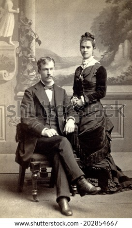 USA - MINNESOTA - CIRCA 1880 Vintage Carte de Viste photo of young couple. The gentleman is sitting and the lady is standing dressed in a Victorian style dress. Photo from Victorian era. CIRCA 1880