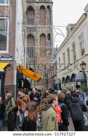 Utrecht, the Netherlands - February 13, 2016: People walking in historic city centre. View to Dom Tower of the St. Martins Cathedral