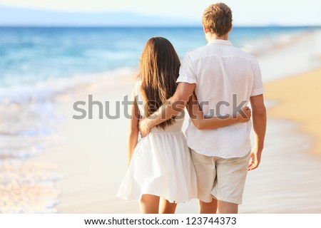 Vacation couple walking on beach together in love holding around each other. Happy interracial young couple, Asian woman and Caucasian man.