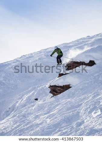 VAIL, CO - JANUARY 2, 2016: Man skiing off rocky cliff on sunny day