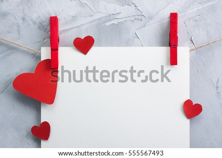 Valentine, love background with white sheet of paper and red paper hearts hanging 