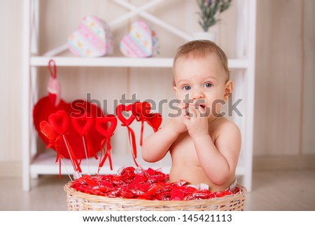 valentine's day. boy in a basket with candy and hearts