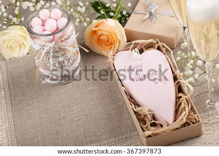 Valentine's Day heart in a gift box, candy, champagne and roses on the tablecloth