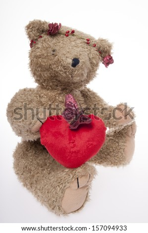 Valentine's Day Teddy bear with flowers and a red heart isolated on white background