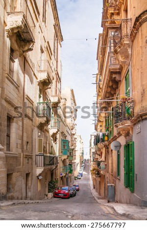 VALLETTA, MALTA - FEBRUARY 20, 2010. Ancient Christopher street in Valletta, Malta. Narrow street with old fashioned balcony, carved stone walls and arches.