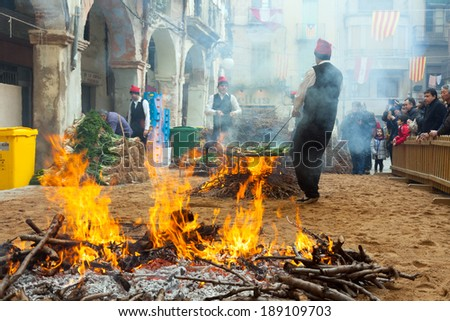 VALLS, SPAIN - JANUARY 26, 2014: Calcotada - popular gastronomical event in Catalonia. Cooking onion on bonfire during Calcotada in Valls