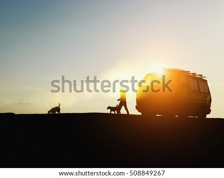 Van with a woman walking her dogs at sunset