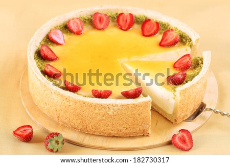Vanilla Cheesecake with strawberries and pistachios, on a yellow background.