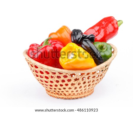 varicolored peppers in basket on white background