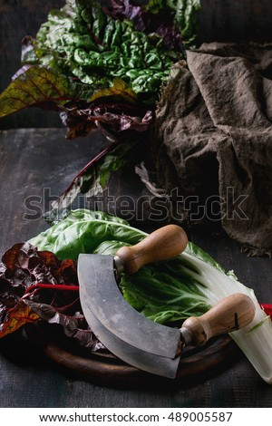Variety of fresh chard mangold salad leaves on woode chopping board with vintage knife and sackcloth rag over old dark wooden background. Dark rustic style. Healthy eating theme.