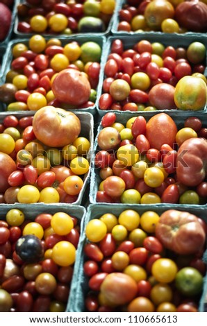 Variety of garden fresh tomatoes in baskets at an open air farmers market.
