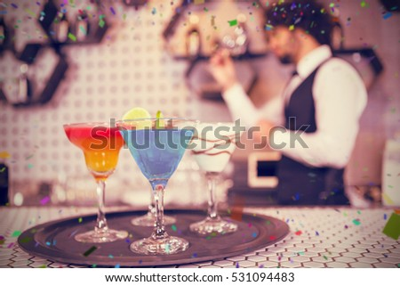 Various cocktails on serving tray in bar counter against flying colours