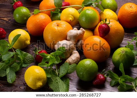 Various fruits scattered on a wooden base. Fresh mint and citrus fruit.
