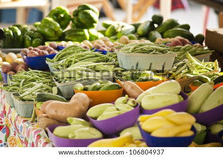 Various healthy vegetables at an open air farmers market featuring beans, potatoes, squash, cucumbers, peppers, and more