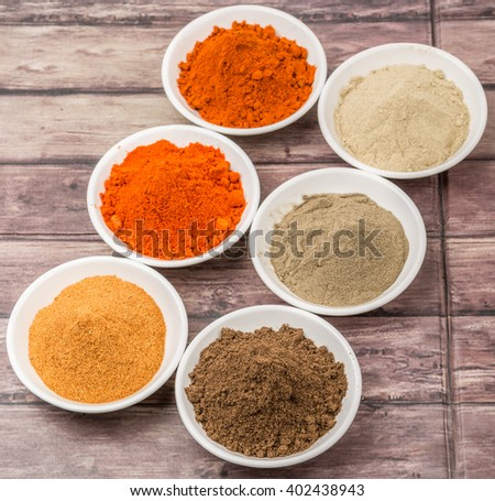 Various hot and spicy spices powder in white bowl over wooden background
