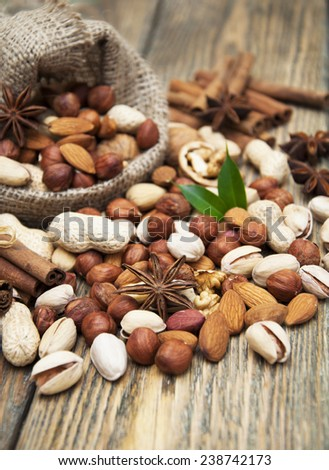 Various nuts in jute sack cinnamon sticks, star anise on a wooden background